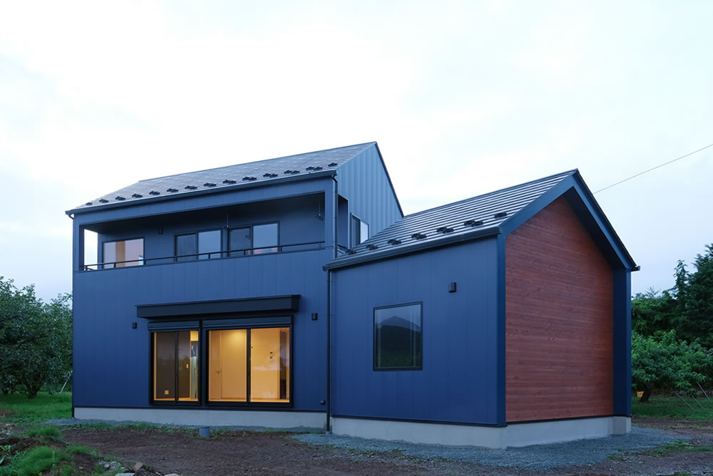 二つの棟が変形角度で構成された家。経年変化を楽しめる板張りのファサードが私たちらしさ。
