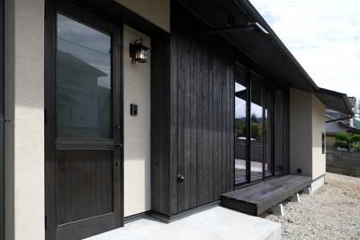 手づくりの玄関ドア。左官と焼杉の外壁